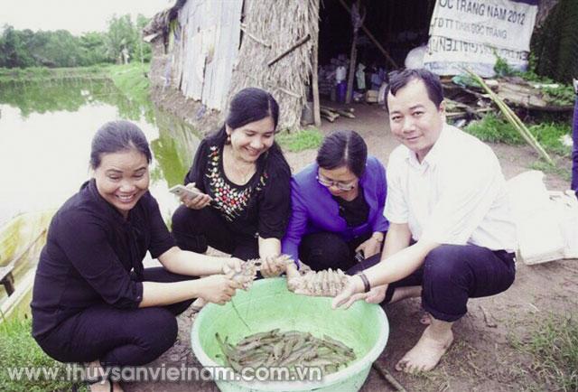 Thứ 2 và 4 từ trái qua, bà Mai Thi và ông Trần Đình Luân cùng cán bộ nông nghiệp kiểm tra tôm nuôi khảo nghiệm ở xã Tham Đôn, huyện Mỹ Xuyên      Ảnh: Xuân Trường